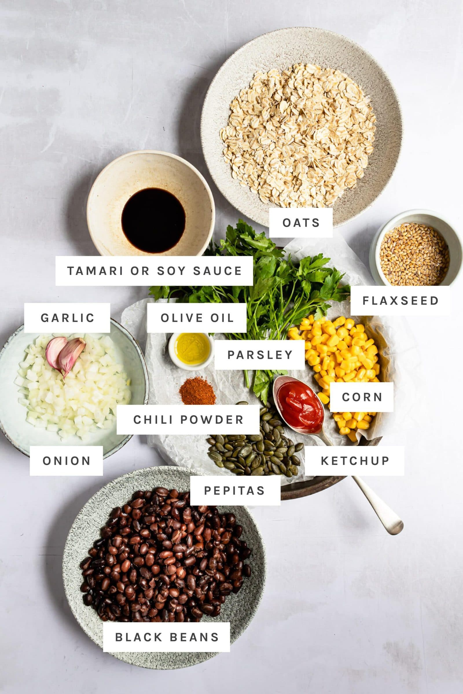 Ingredients to make black bean burgers with labels including beans, veggies, oats and spices.
