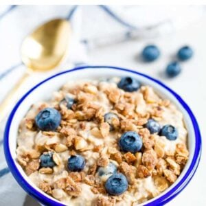 Bowl of blueberry overnight oats topped with a crumble topping and blueberries.