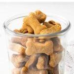 وعاء زجاجي مليء بزبدة الفول السوداني يعامل الكلب على شكل العظام.