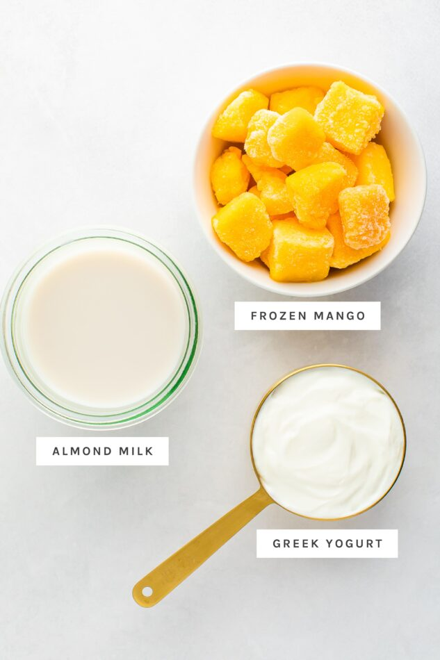 Frozen mango, almond milk and greek yogurt measured out in bowls and a measuring cup.