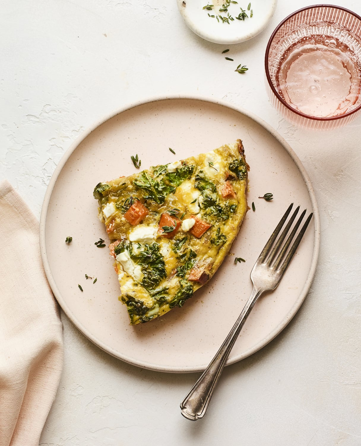 Slice of sweet potato kale frittata on a plate with a fork.