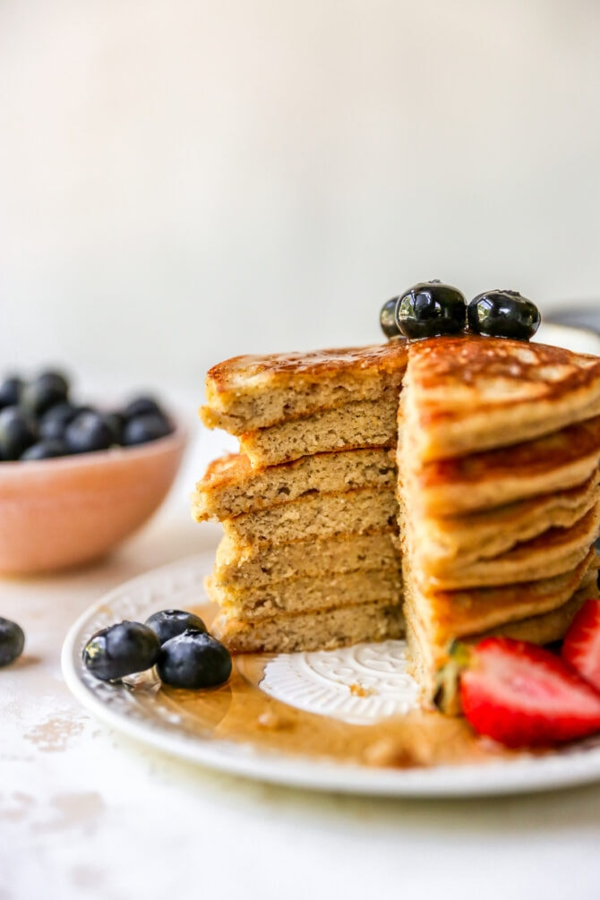Stack of almond flour pancakes served with berries and maple syrup. A slice is taken out of the pancake stack.