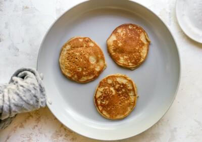 Three almond flour pancakes in a frying pan.