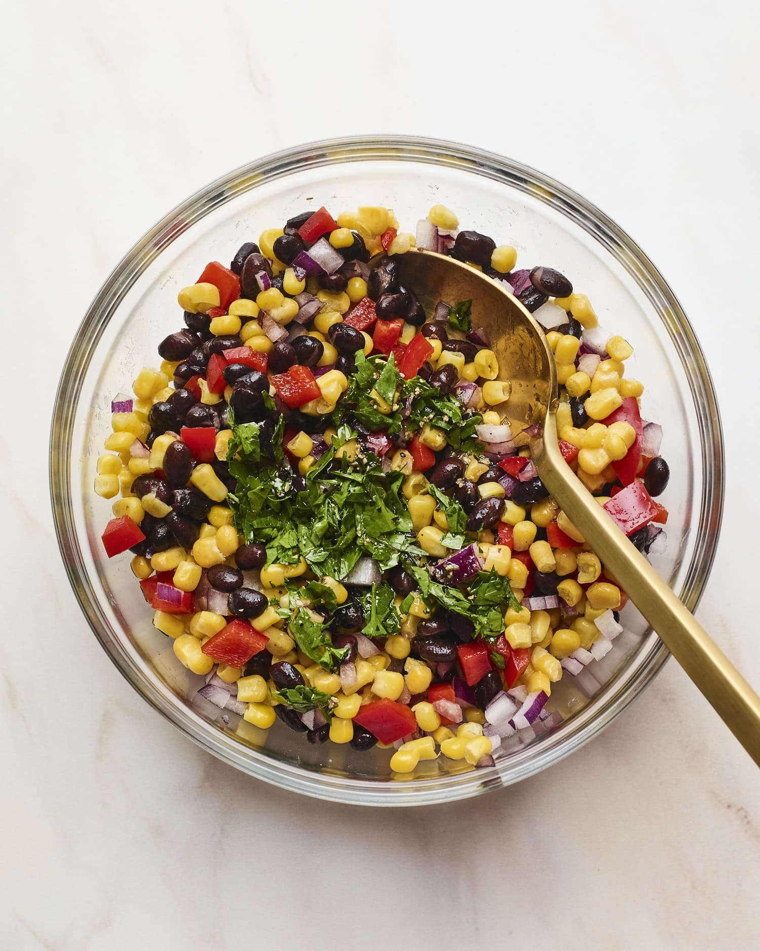 Mixing bowl with black bean and corn salad with a spoon and topped with cilantro.