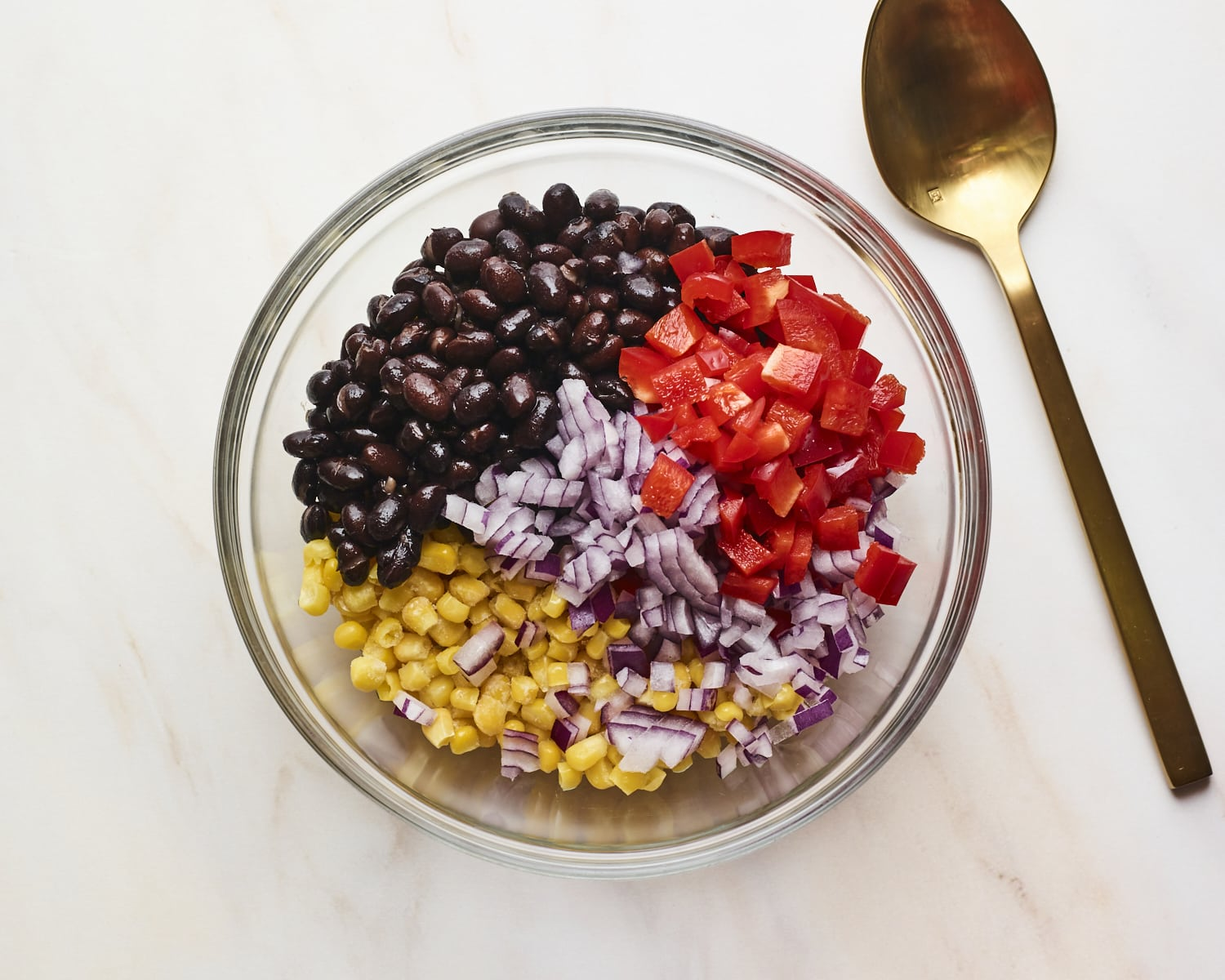 Mixing bowl with chopped pepper, onion, corn and black beans before being mixed.