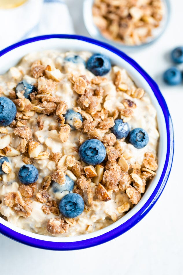 Blueberry overnight oats in a white and blue bowl with oatmeal crumble and blueberries on top.