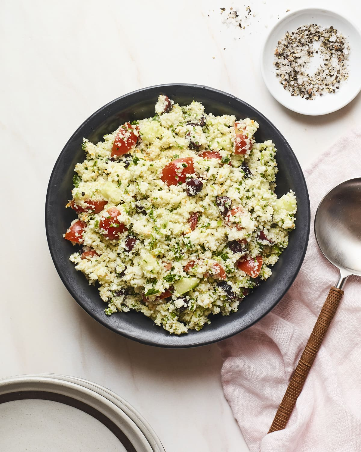 Serving plate with cauliflower tabbouleh. Salt and pepper and a serving spoon are beside the plate.