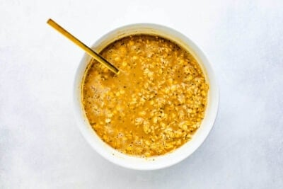 Ingredients to make coffee overnight oats in a bowl all mixed together with a gold spoon.