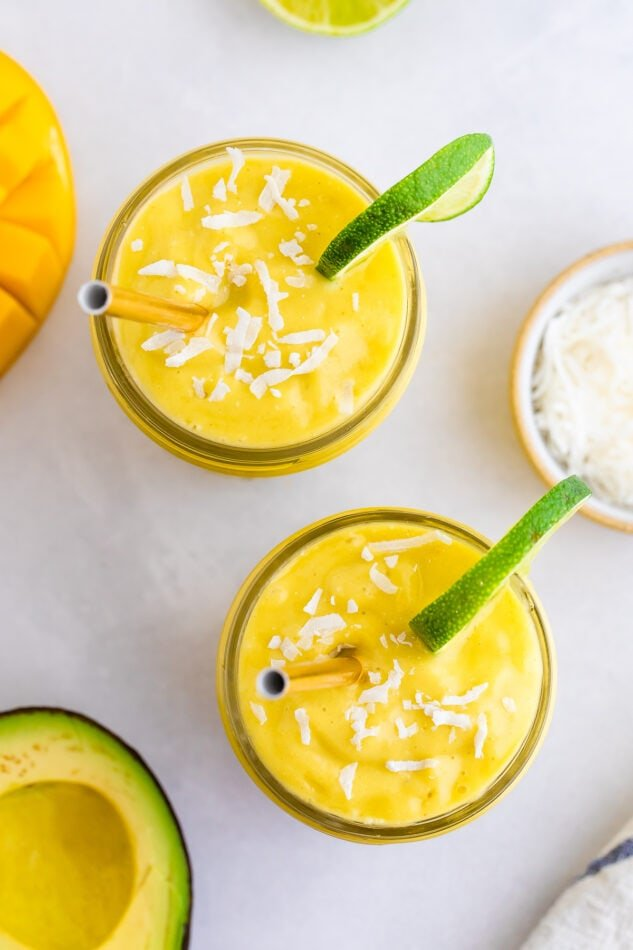 Two glasses with avocado mango smoothie garnished with coconut and lime slices.