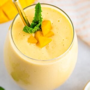 Mango smoothie in a glass with a metal straw and garnished with mint and mango chunks.