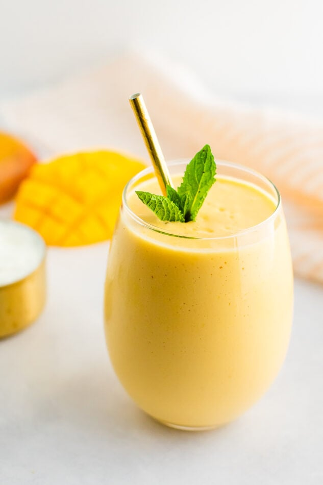 Mango smoothie in a glass with a metal straw and garnished with mint.