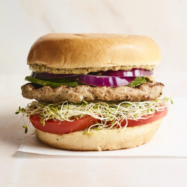 Spinach and feta turkey burger on a bun with avocado, onions, tomatoes and sprouts.