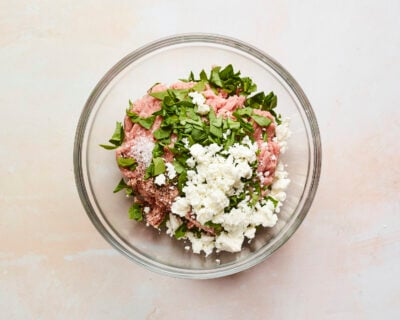 Mixing bowl with ground turkey and feta and spinach added on top.
