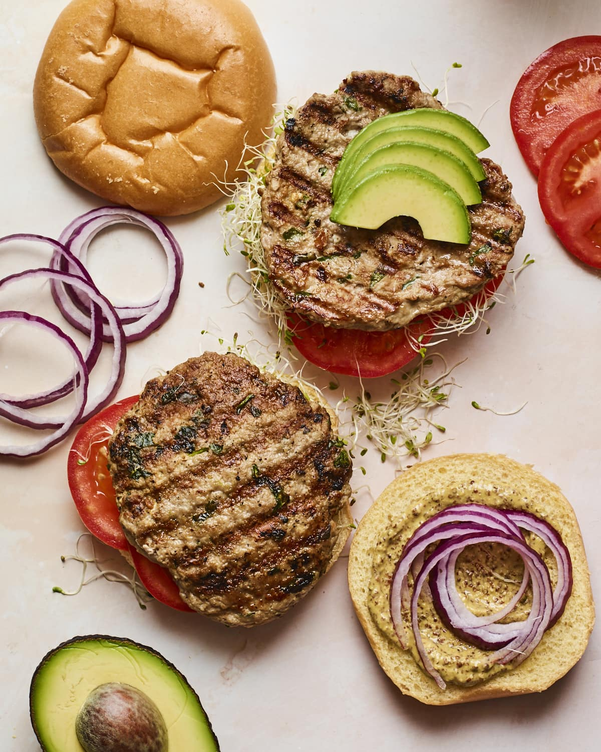 Two open faced spinach and feta turkey burgers with burger toppings and buns around on the table.