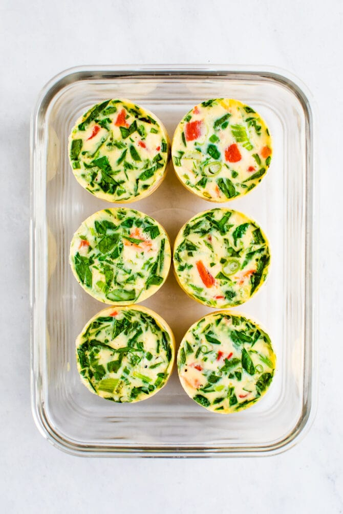 6 egg white bites made with spinach and red pepper in a glass food storage container.