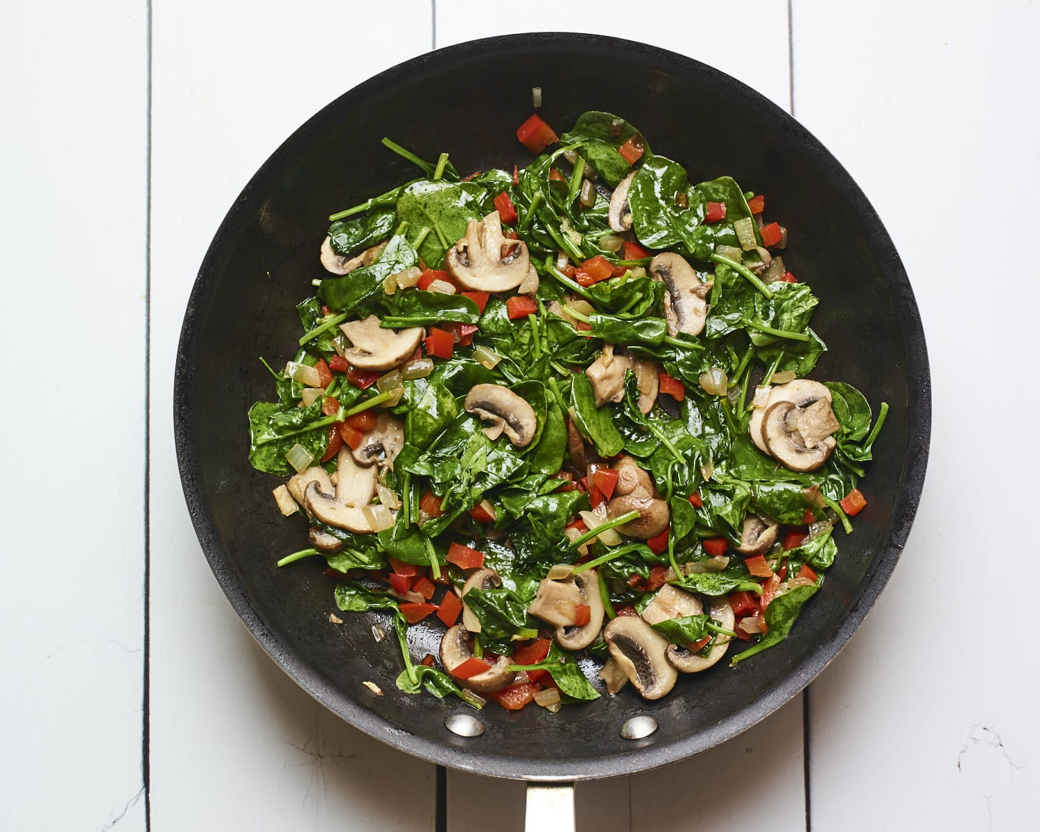 Skillet with bell pepper, mushrooms and spinach.