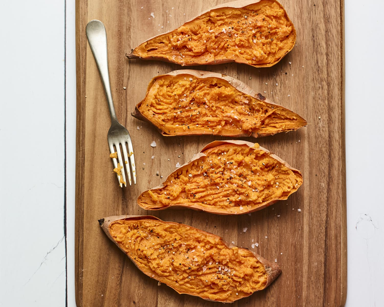 Four sweet potato halves on a wood cutting board.