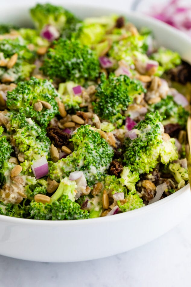 Side angle view of vegan broccoli salad in a white bowl.