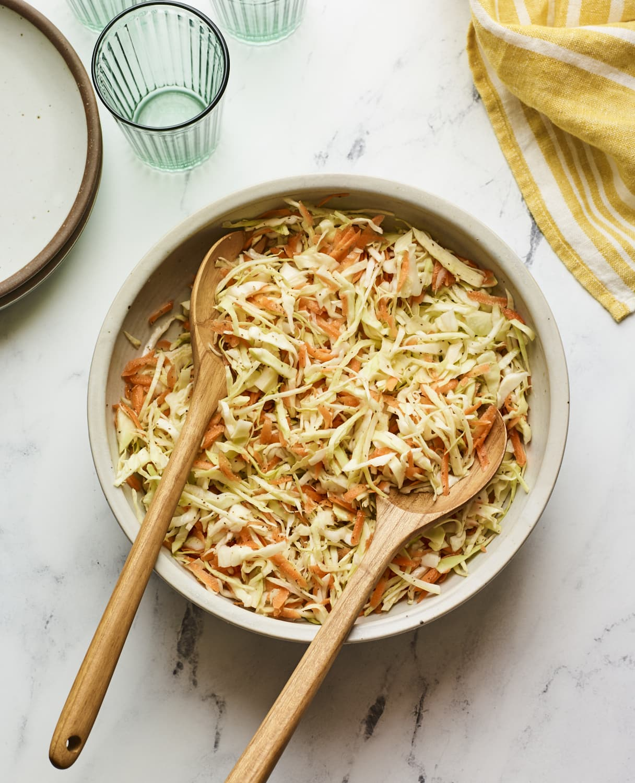 Serving bowl of apple cider vinegar coleslaw with wood serving spoons.