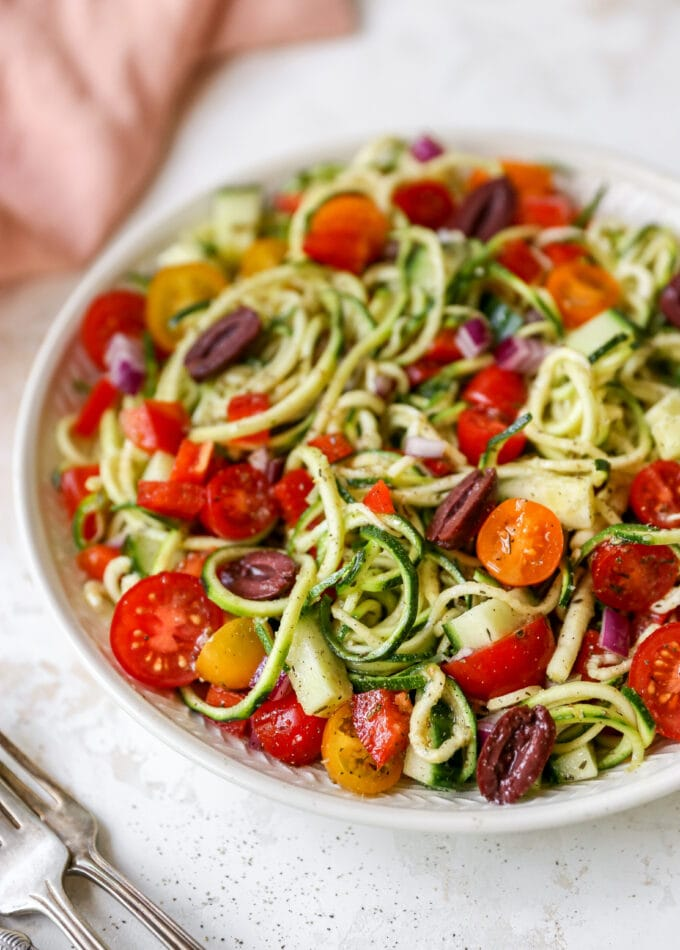 Serving bowl of zucchini noodle salad with tomatoes, peppers and olives.