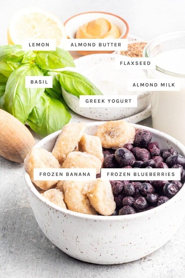 Lemon, almond butter, flaxseed, almond milk, Greek yogurt, basil, frozen banana and frozen blueberries measured out.