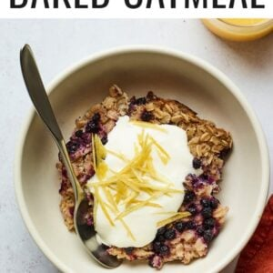 Serving of blueberry lemon baked oatmeal in a bowl and topped with yogurt and lemon zest.