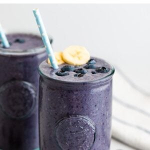 Blueberry smoothie topped with blueberries, banana and a straw.