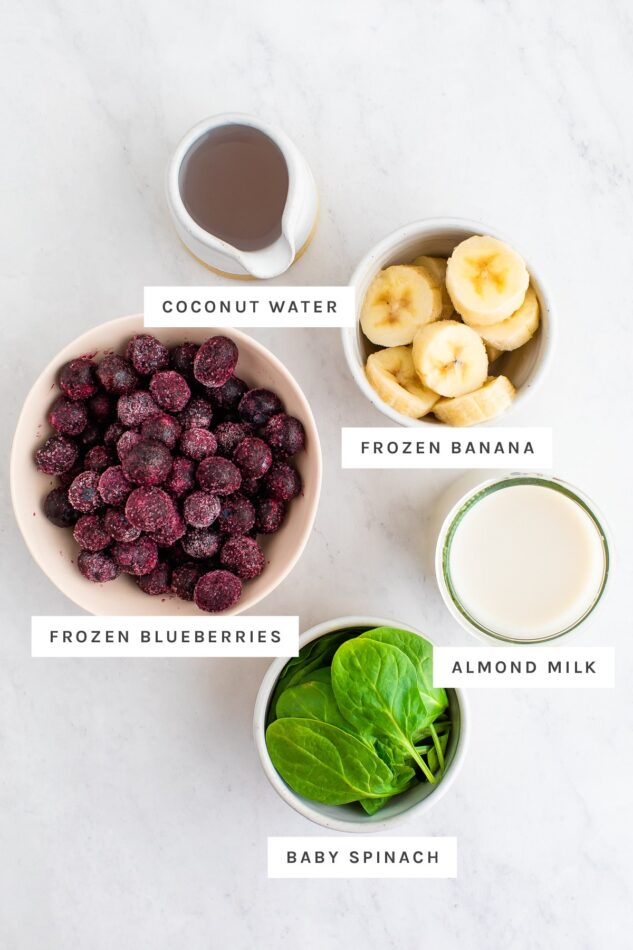 Coconut water, frozen banana, frozen blueberries, almond milk and baby spinach measured out in bowls.