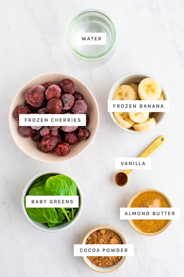 Water, frozen cherries, frozen banana, vanilla, baby greens, almond butter and cocoa powder measured out in bowls.