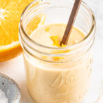 Citrus tahini dressing in a jar, topped with orange zest.