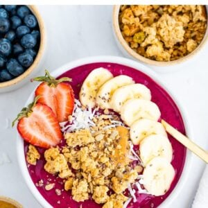 Dragon fruit smoothie bowl topped with granola, banana slices and a strawberry.