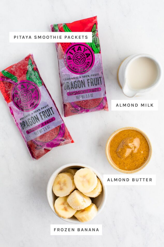 Pitaya smoothie packets, almond milk, almond butter and frozen banana measured out.