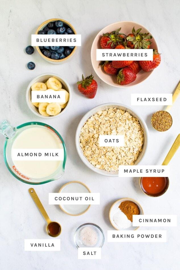التوت والموز والشوفان وحليب اللوز والمكونات الأخرى التي تم قياسها لصنع دقيق الشوفان المخبوز.