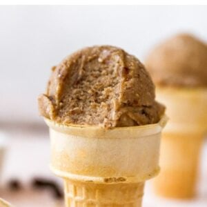 Scoop of oatmeal raisin banana ice cream in a cake cone. Ice cream has a bit taken out of it.
