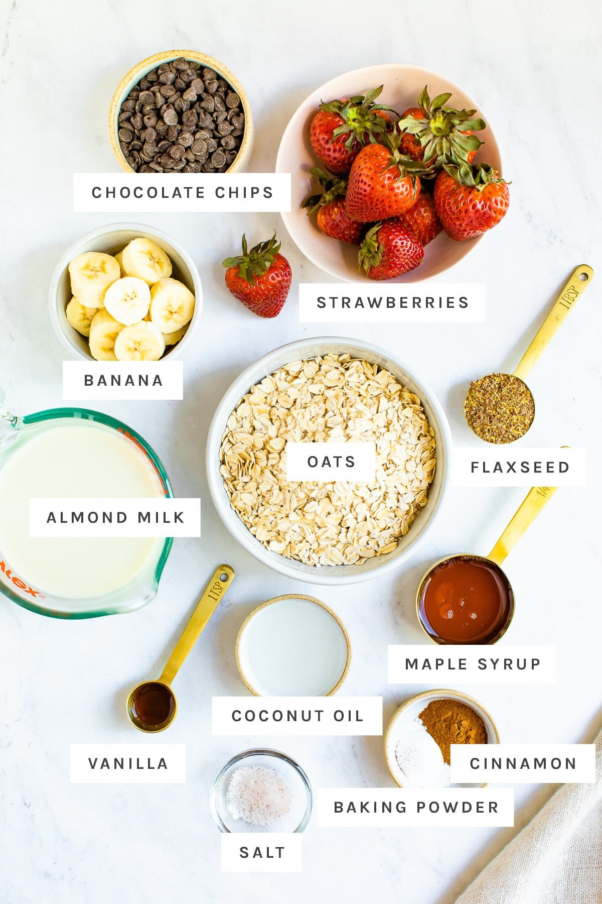 Strawberries, banana, chocolate chips, oats and other ingredients measured out to make strawberry banana baked oatmeal.