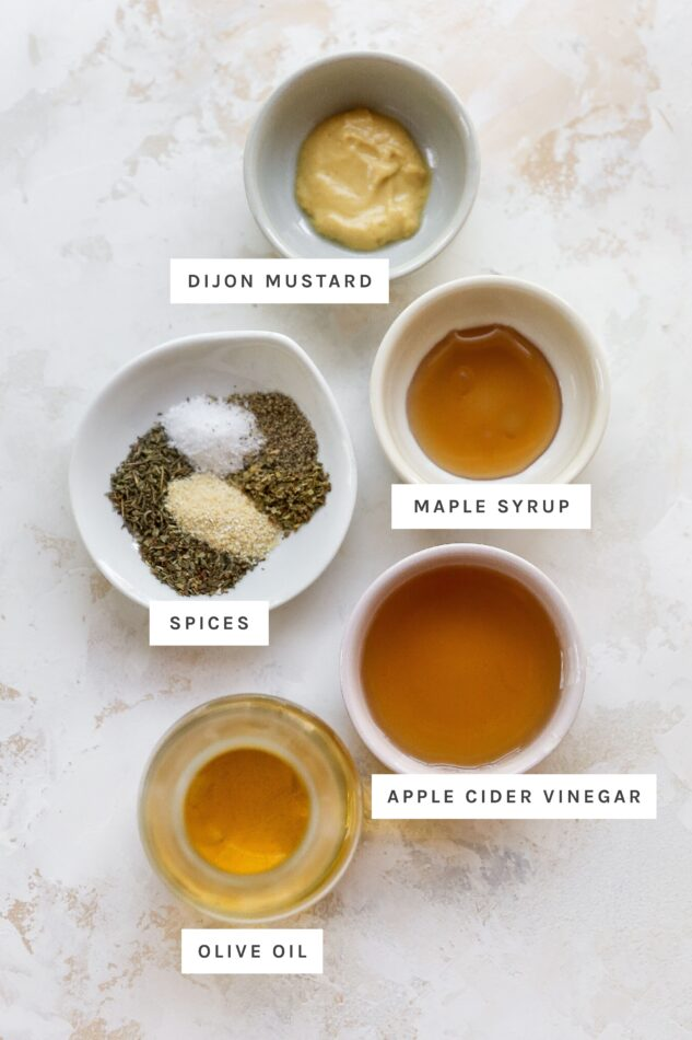Dijon, maple syrup, vinegar, olive oil and spices measured out in bowls to make italian dressing.