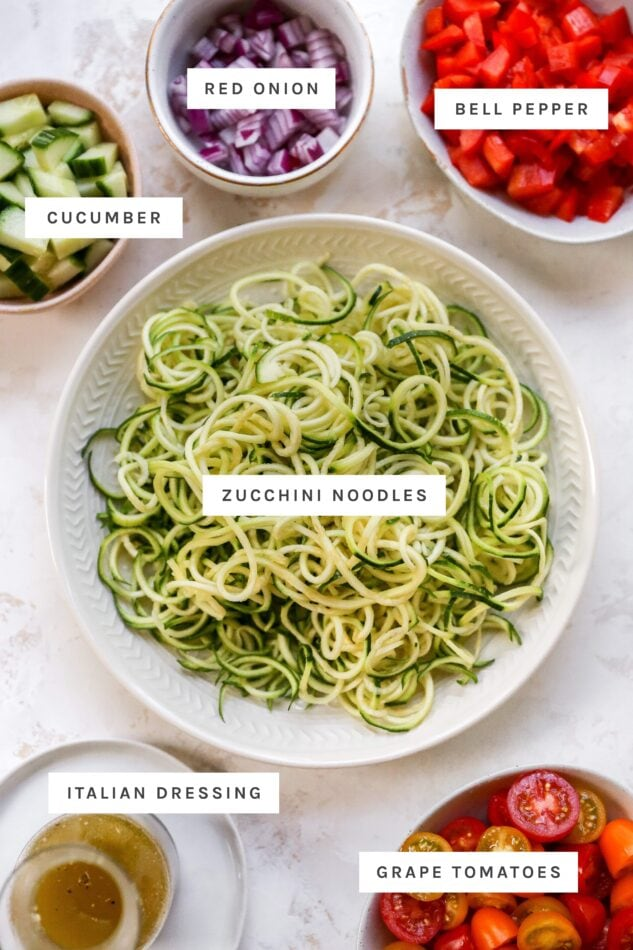 Cucumber, red onion, bell pepper, zucchini noodles, dressing and tomatoes measured out into bowls to make zucchini noodles.