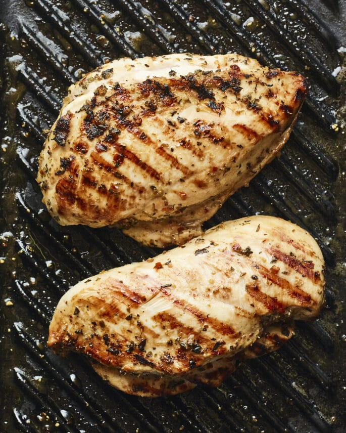 Two well-seasoned chicken breasts on a grill pan with grill marks