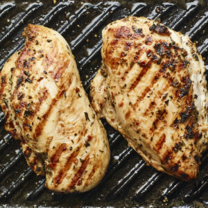Two chicken breasts grilling on a grill pan.