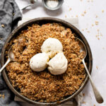 Round dish with an apple crisp topped with three scoops of vanilla ice cream. Two serving spoons are in the crisp.