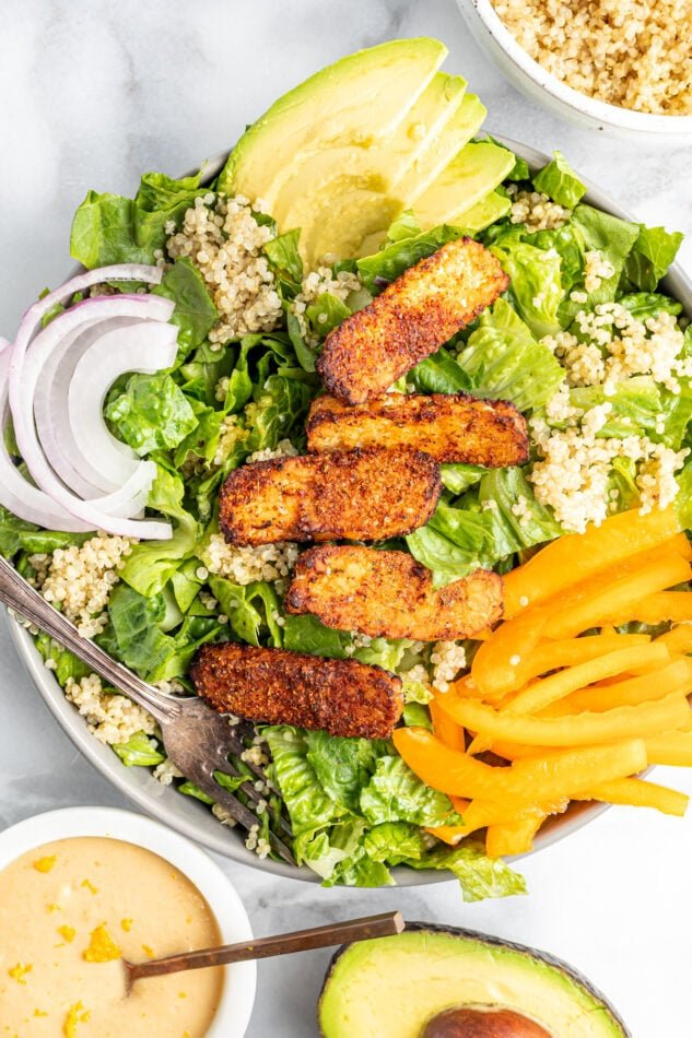 Salad topped with blackened tempeh, peppers, onions, avocado and quinoa.