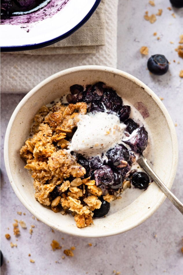 Blueberry crumble topped with vanilla ice cream in a bowl with a spoon.