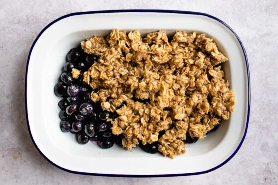 Blueberries in a baking dish getting topped with an oatmeal crumble.