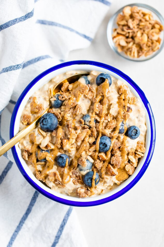 Blueberry overnight oats in a white bowl with blue rim. Topped with blueberries, crumble and nut butter.