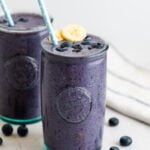 Blueberry smoothie in a glass topped with blueberries, banana slices and a straw.