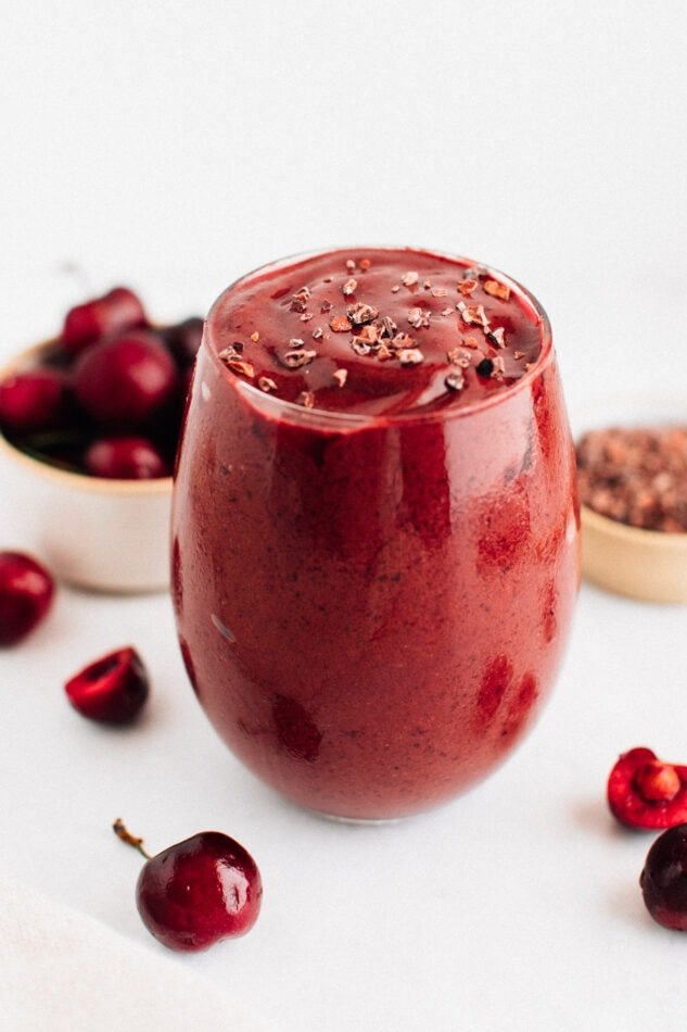 Chocolate cherry smoothie in a glass and topped with cacao nibs.