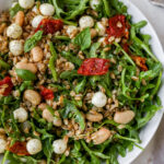 Farro salad with arugula, beans, tomatoes and mozzarella in a serving bowl.
