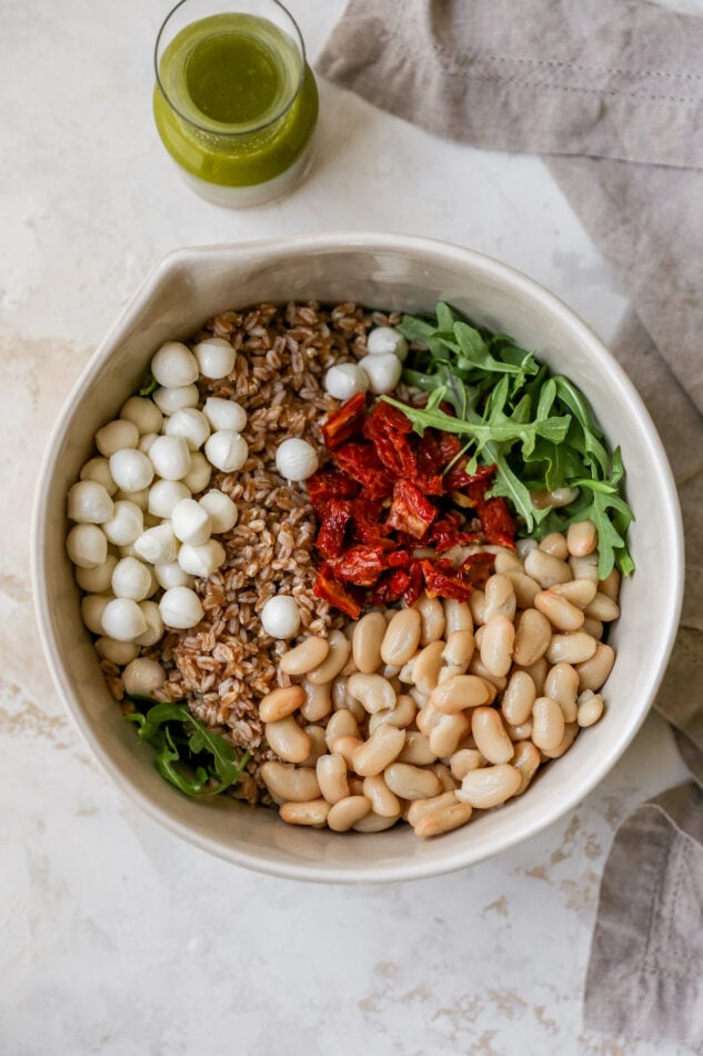 Mozzarella balls, farro, arugula, sun-dried tomatoes and beans in a bowl. A jar of basil vinaigrette is to the side of the bowl.