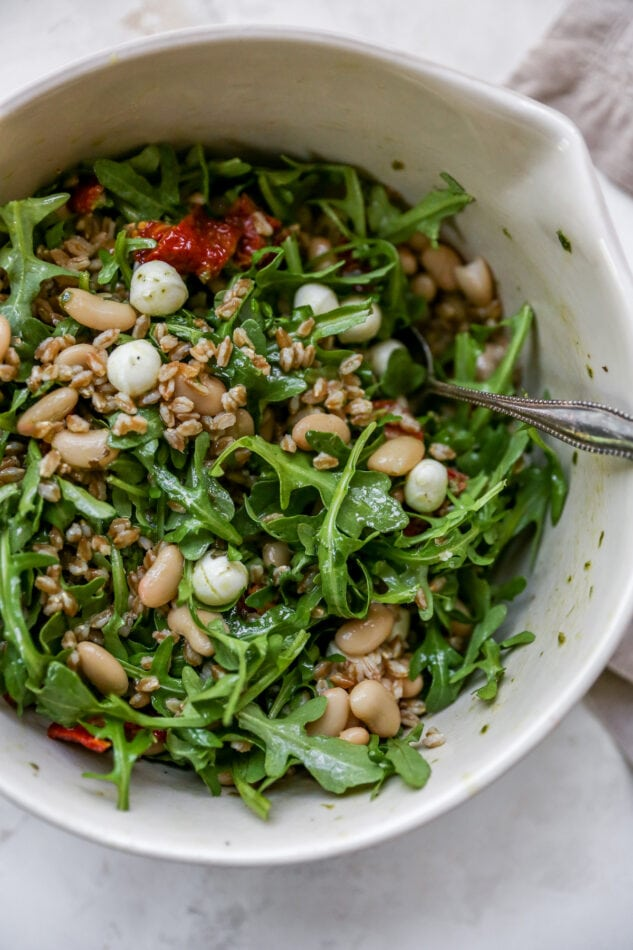 Farro salad with arugula, beans, tomatoes and mozzarella in a mixing bowl with a spoon.