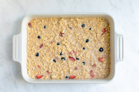 Baked oatmeal mixture with berries in a baking dish before being baked.